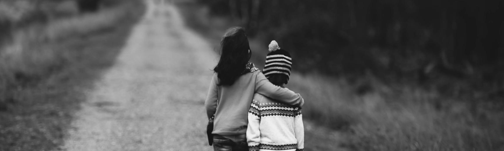 A black and white photo of two small children walking down a track, away from the camera. The bigger child has their arm around the smaller one, as if comforting them.