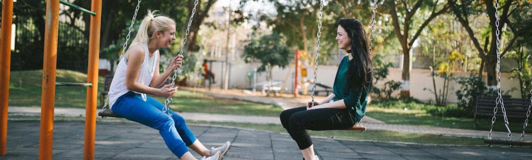 Friends sit on park swings