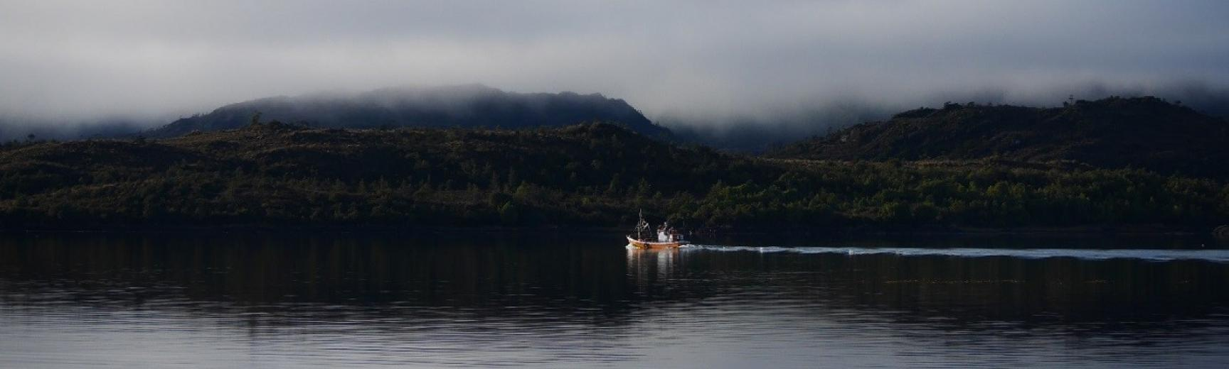 people in a boat on a river in Chile with mountains in the background
