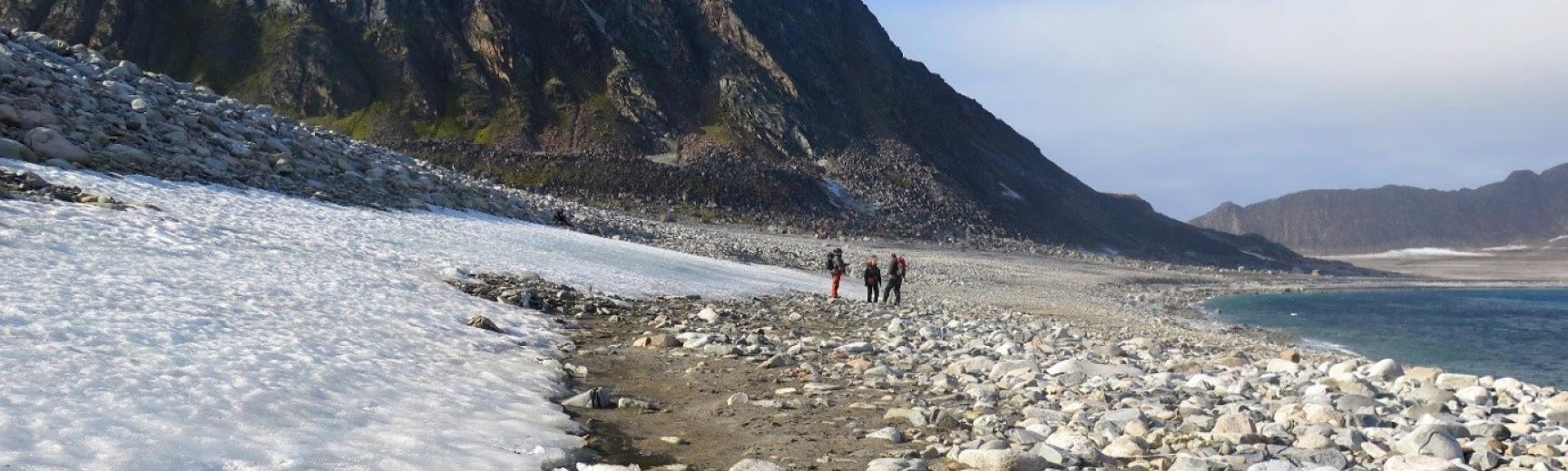 Three people walk across a beach in the artic. There is snow on the left and a moutain in the background.