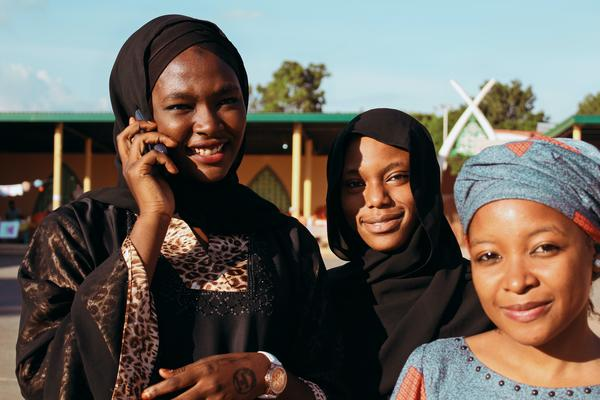 Young Nigerian women smiling, one using a mobile phone