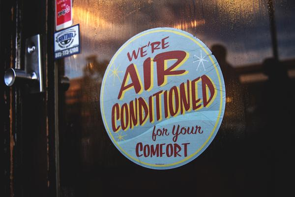 """A poster in a shop window reads """"We're air conditioned for your comfort"""". The window is dripping in condensation, implying that it is hot and that air conditioning is necessary."""