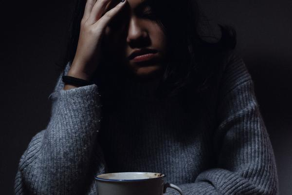 A young woman sits in a dark room with her head in one hand, leaning over a cup of tea