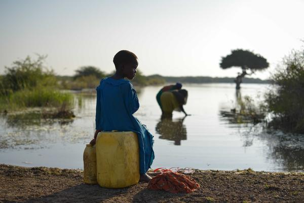 A young African child sits on a plastic water container at the edge of a river while two other figures collect water.