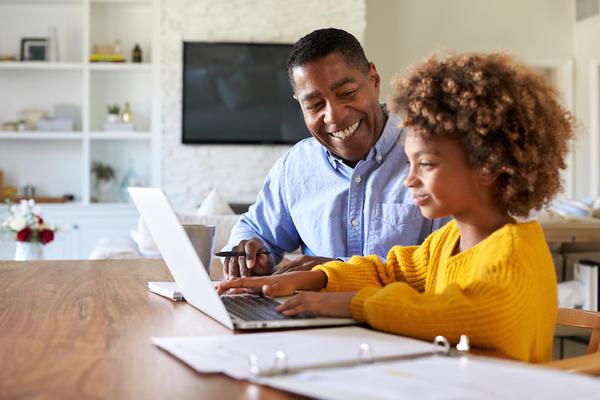 Parent home-schooling a child at a laptop