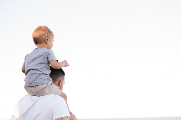 A young boy sits on his father's shoulders. The father is holding the boy's ankles to stabilise him while the boy has his hands in the air.