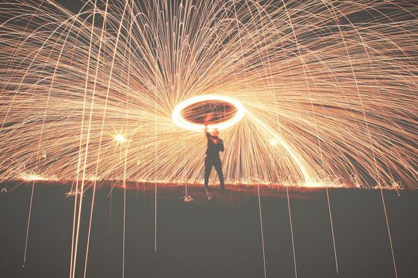 A man swings a flame above his head creating a spinning circle of light from which many sparks fly