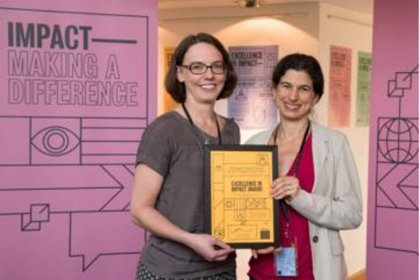 Professor Lucie Cluver and Joy Todd, Head of Health and Human Behaviour research at the ESRC, smile for the camera as they hold the project's prize certificate
