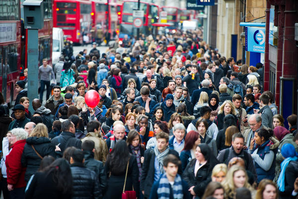 A busy London street full of people. One person carries a red balloon.
