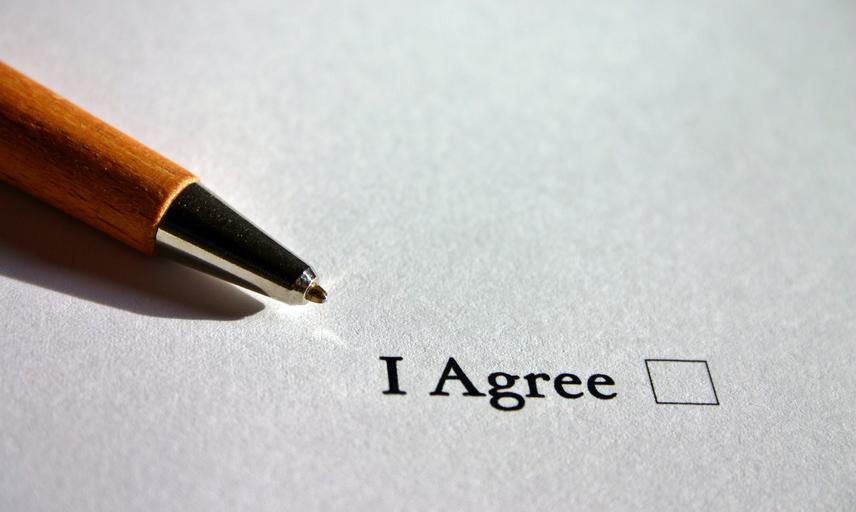 "A pen rests on a sheet of paper printed with the words ""I agree"" and a check box"