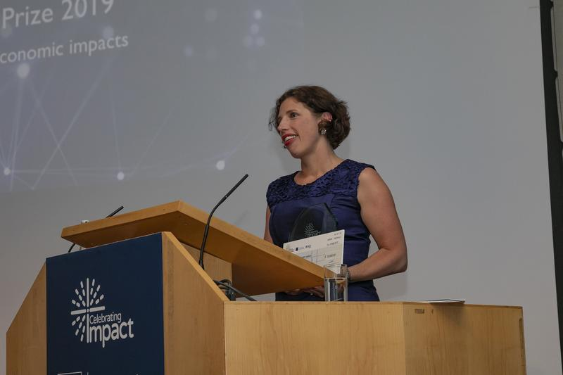 Shona Minson stands at a podium to give a speech at the ESRC impact awards