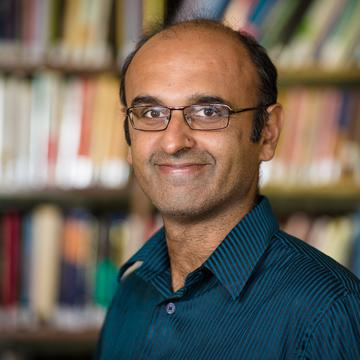 Portrait photo of Professor Yadvinder Malhi, smiling against a blurred background of shelves full of books