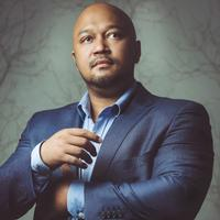 Eusebius McKaiser stands in a blue suit and shirt against a grey wall. His arms are raised
