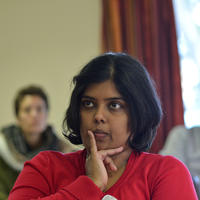 Usha kanagaratnam is photographed listening in a meeting, with her hand on her chin